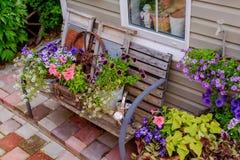 Porche admirablement décoré d'une maison privée, fleurs colorées dans de grands pots d'argile, banc de vintage, inventaire de vin photographie stock