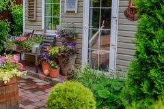 Porche admirablement décoré d'une maison privée, fleurs colorées dans de grands pots d'argile, banc de vintage, inventaire de vin photos stock