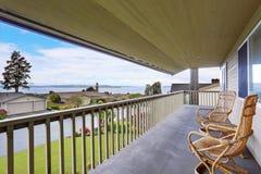 Porche couvert confortable avec les chaises en osier et les balustrades en bois photos stock