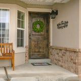 Porche de accueil de place d'une maison avec le banc brun devant la demi fenêtre d'hexagone photographie stock libre de droits