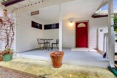 Porche gentil avec un ensemble rouge de porte et de table photographie stock