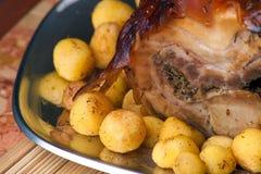 Porchetta italiano con las nuevas patatas Fotos de archivo