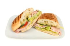 Porchetta panini portions. Porchetta and salad panini portions on a plate isolated against white stock image
