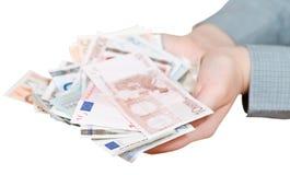 Porción de billetes de banco euro en las palmas ahuecadas aisladas Fotos de archivo