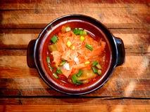 Porción de col guisada con pimienta dulce y cebollas verdes en un pote de arcilla en un tablero de madera Imagen de archivo