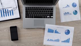 Porción de gráficos para analizar la mentira en el escritorio en la oficina del hombre de negocios, visión superior imagen de archivo