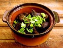 Porción de hígado frito de la carne de vaca en pedazos grandes con las cebollas verdes tajadas en un pote de arcilla en un tabler Imagen de archivo libre de regalías