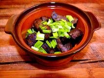 Porción de hígado frito de la carne de vaca en pedazos grandes con las cebollas verdes tajadas en un pote de arcilla en un tabler Imágenes de archivo libres de regalías