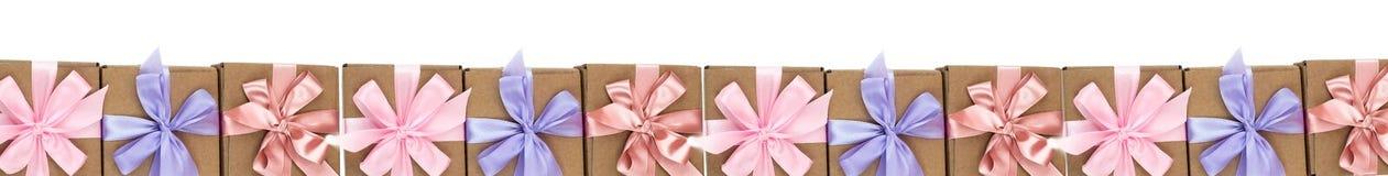 Porción de la bandera de cajas del día de fiesta con los regalos atados con la cinta de satén en un fondo blanco Foto de archivo
