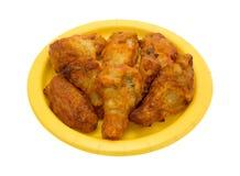 Porción de las alas de pollo en una placa de papel amarilla Fotos de archivo libres de regalías