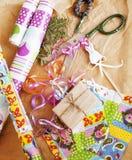Porción de materia para los regalos hechos a mano, tijeras, cinta, papel con el co Imágenes de archivo libres de regalías