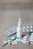 Porción de medicación y de píldoras coloridas desde arriba en fondo de madera gris Todos para la gripe - espray nasal, vitaminas, Imagen de archivo