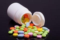Porción de píldoras coloridas con la caja blanca en fondo negro Imagen de archivo libre de regalías