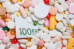 Porción de píldoras y de cientos billetes de banco del euro Foto de archivo