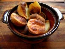 Porción de patatas cocidas en pedazos grandes en un pote de arcilla en un tablero de madera Imagen de archivo libre de regalías