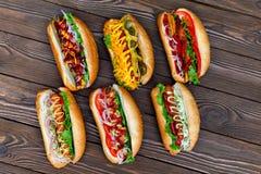 Porción de perritos calientes deliciosos grandes con la salsa y las verduras Fotografía de archivo libre de regalías