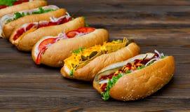 Porción de perritos calientes deliciosos grandes con la salsa y las verduras en fondo de madera Fotografía de archivo libre de regalías