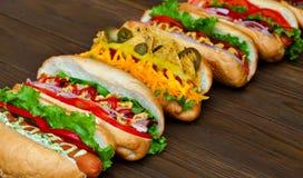 Porción de perritos calientes deliciosos grandes con la salsa y las verduras en fondo de madera Fotos de archivo