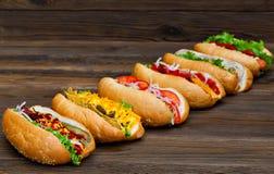 Porción de perritos calientes deliciosos grandes con la salsa y las verduras en fondo de madera Imágenes de archivo libres de regalías