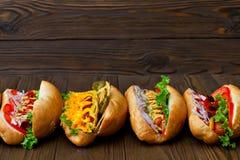 Porción de perritos calientes deliciosos grandes con la salsa y las verduras en fondo de madera Imagenes de archivo