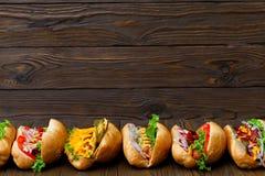 Porción de perritos calientes deliciosos grandes con la salsa y las verduras en fondo de madera Fotos de archivo libres de regalías