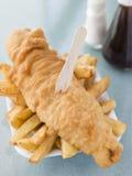 Porción de pescado frito con patatas fritas en una bandeja del poliestireno foto de archivo