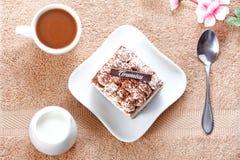 Porción de postre del tiramisu y de una taza de café Imagen de archivo libre de regalías