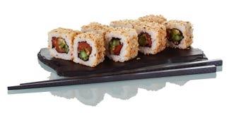 Porción de rollos de sushi japoneses en la placa especial y los palillos aislados en blanco Imagen de archivo libre de regalías