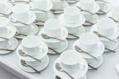 Porción de tazas con las cucharas blancas en una tabla, para el café o el té Foto de archivo libre de regalías
