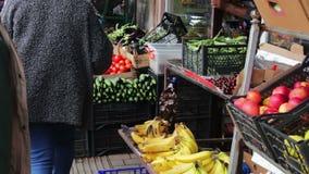 Porción de verduras frescas en el contador del mercado Los compradores miran la opción de los tomates frescos, patatas, pimientas metrajes