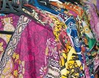 Porción de vestidos coloridos en suspensiones Imágenes de archivo libres de regalías