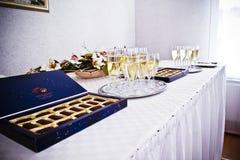 Porción de vidrios con champán durante en la tabla del partido foto de archivo libre de regalías
