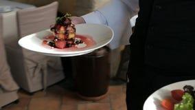 Porción del camarero en el movimiento de servicio en restaurante almacen de metraje de vídeo