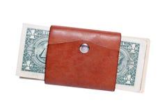 Porción del primer de billetes de banco americanos del dólar en pequeña cartera marrón de cuero cerrada con el botón Salto del co foto de archivo libre de regalías