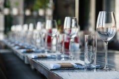 Porción del restaurante, vidrios de cristal del vino y de agua, bifurcaciones y kniv imagenes de archivo