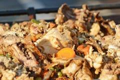 Porción grande de pollo asado a la parrilla con las verduras en cocinar al aire libre de la cacerola grande de la parrilla Imágenes de archivo libres de regalías