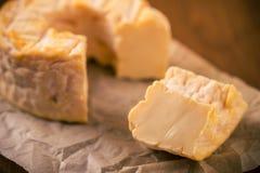 Porci cięcie od całego złotego camembert sera na papieru prześcieradle Obraz Royalty Free