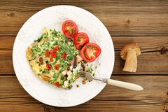 Porcini mushrooms omelette with tomatoes and scallion with whole Royalty Free Stock Photos