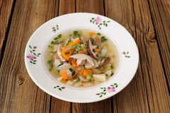 Porcini mushrooms soup in white plate on wooden background copys Stock Image