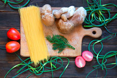 Porcini, spaghetti, arrows of garlic, tomatoes, parsley on dark. Wooden background. Rustick stile. concept of food Royalty Free Stock Images