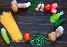 Porcini, spaghetti, arrows of garlic, tomatoes, parsley, lettuce. And cucumber on dark wooden background. Rustick stile. concept of food Royalty Free Stock Images