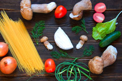 Porcini, spaghetti, arrows of garlic, tomatoes, parsley, lettuce. Onion, chees and cucumber on dark wooden background. Rustick stile. concept of food Stock Photos