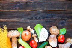 Porcini, spaghetti, arrows of garlic, tomatoes, parsley, lettuce. Onion, chees and cucumber on dark wooden background. Rustick stile Royalty Free Stock Image