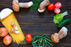 Porcini, spaghetti, arrows of garlic, tomatoes, parsley, lettuce. Onion, cheese and cucumber on dark wooden background. Rustick stile. Food concept Royalty Free Stock Photo