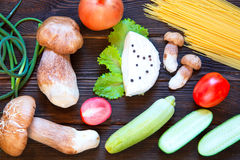 Porcini, spaghetti, arrows of garlic, tomatoes, parsley, lettuce. Onion, cheese and cucumber on dark wooden background. Rustick stile. Food concept Royalty Free Stock Photos