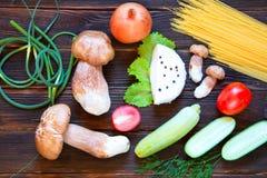 Porcini, spaghetti, arrows of garlic, tomatoes, zucchini, parsle. Food ingredients on dark wooden background. Rustick stile Stock Photos