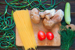 Porcini, spaghetti, arrows of garlic, tomatoes, zucchini, parsle. Y on dark wooden background. Rustick stile. Food concept Stock Photos