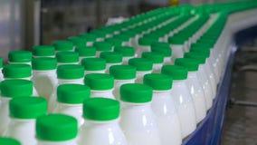 Porciones de botellas con la leche que mueve encendido un transportador en la fábrica metrajes