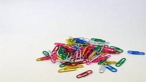 Porciones de clips de papel coloridos en un fondo blanco foto de archivo libre de regalías