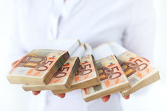 Porciones de dinero en pilas foto de archivo